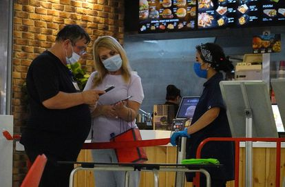 An employee checks the QR code of a citizen in a fast food establishment in Moscow, this Monday.