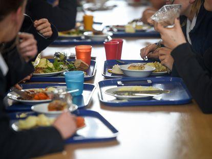 Varios estudiantes comen en sus bandejas en una escuela británica.