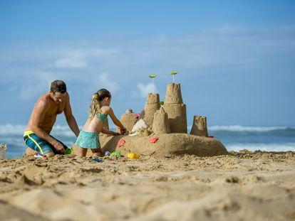 Un hombre y su hija construyen un castillo de arena en una playa de Hawai, en Estados Unidos,