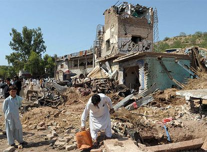 Residentes paquistaníes recogen escombros tras la explosión de una bomba en la ciudad de Kohat.