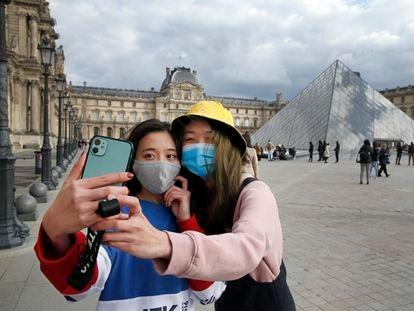 Dos mujeres con máscara protectora ante el Museo del Louvre en París, el 6 de marzo