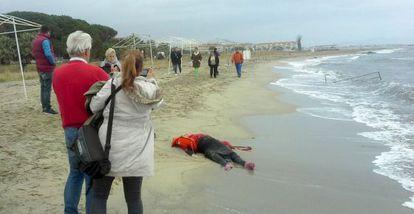 Dos personas fotografían a una víctima en Ayvalik (Turquía)