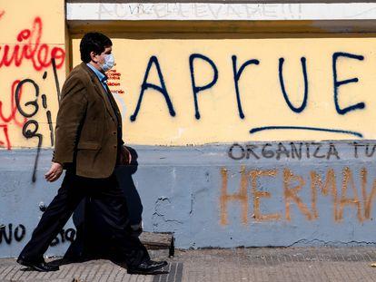 Un hombre camina delante de una pintada callejera a favor de la opción por el sí a la reforma de la Constitución heredada de Pinochet, en Santiago, el 26 de agosto.