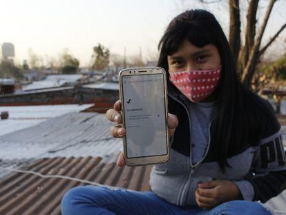 La hija de Soledad Delgado sostiene el único celular que tiene la familia para conectarse en Villa Fátima, en Buenos Aires (Argentina).