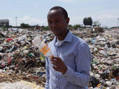 James Wakibia con una botella de plástico encontrada en el vertedero de Gioto, cerca de Nakuru.