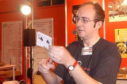Fernando Blasco hace un truco de magia con unos naipes.