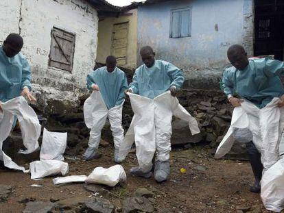 Miembros de la Cruz Roja se visten con los trajes de protección antes de recoger un cadáver en Monrovia (Liberia) en septiembre pasado.