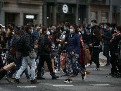 Decenas de personas cruzan el paso de peatones que comunica la plaza de Catalunya con la Rambla en Barcelona.