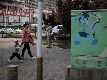 Una mujer y un niño caminan por una calle de Pekín este miércoles