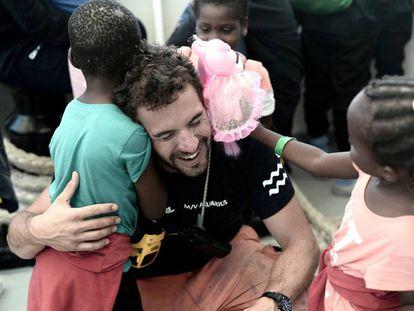 Un miembro de la tripulación del 'Aquarius' abraza a dos niños a la llegada al puerto de Valencia.