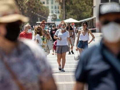 Personas sin mascarilla y con mascarillas en el paseo marítimo de la playa Malvarrosa de Valencia el pasado sábado.