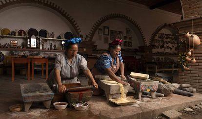 Rosario y Abigail Mendoza (derecha) muelen chile y maíz en el restaurante Tlamanalli, Oxaca.