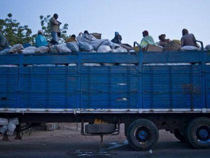 Camión en la ruta dirección al desierto en Malí. El remolque va cargado de sacos de grano sobre los que viajan los pasajeros que quieren llegar a Europa.