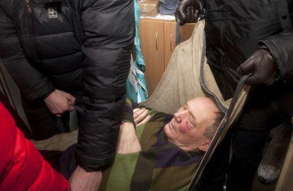 Un grupo de seguidores traslada al poeta Vladímir Nikláyev, candidato en las elecciones presidenciales celebradas hoy en Bielorrusia, tras ser golpeado por agentes de policía cuando participaba en una protesta de la oposición contra el fraude electoral.