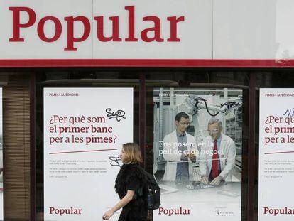 Una mujer pasa por delante de una oficina del Banco Popular, en Barcelona.