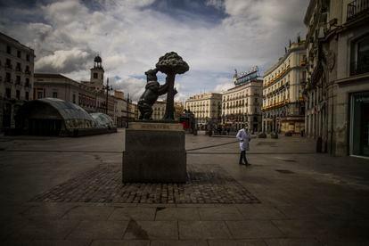 El silencio en las calles. Un hombre con mascarilla camina por la Puerta del Sol, durante el estado de alarma en primavera.