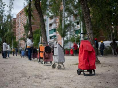 Vecinos a la espera de que una entidad vecinal les entregue alimentos, el sábado en Madrid.