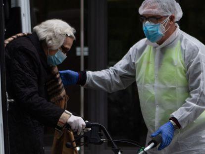 Un voluntario traslada una mujer de una residencia de Barcelona durante la primera ola de la pandemia.