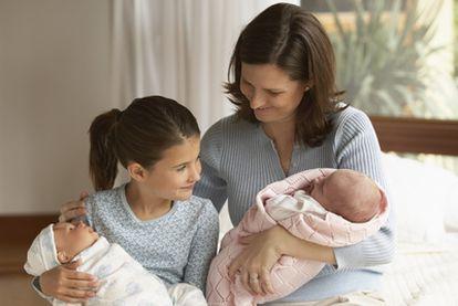 Imagen familiar en la que una niña con un muñeco imita el rol  de su madre con el bebé.