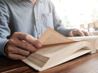 Un hombre pasa las hojas de un libro.