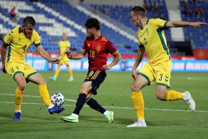 El delantero de la selección española sub21, Javi Puado, controla el balón ante dos jugadores de Lituania.