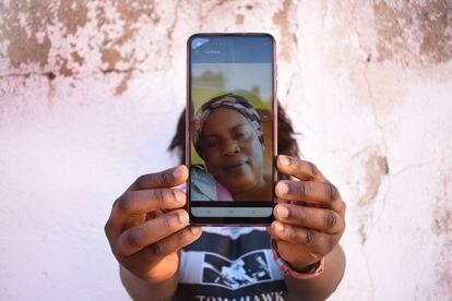 Glad oculta su rostro tras una fotografía de su madre, a quien envía dinero para subsistir en el Congo.