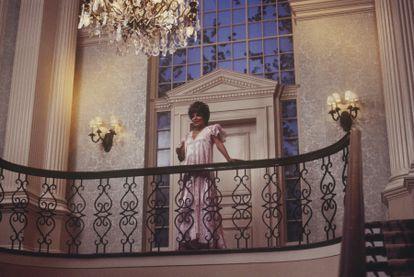 Joan Collins marida con champán su victoria en la cima de la gran escalera de la mansión Carrington, que es lo más semejante al monte del Olimpo, con su frontón neoclásico, en el capítulo en el que prueba con documentos que es la legítima propietaria de la residencia. |