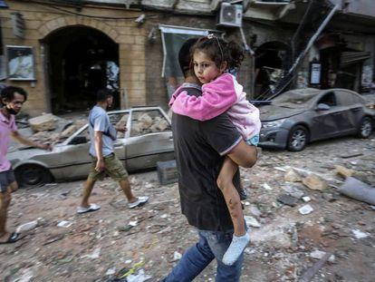 Un hombre lleva en brazos a una niña tras explosión del pasado martes en Beirut.