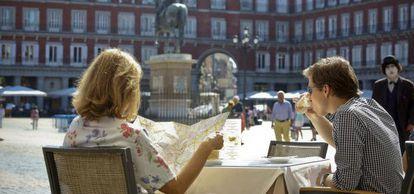 Unos turistas toman un café en la plaza Mayor.