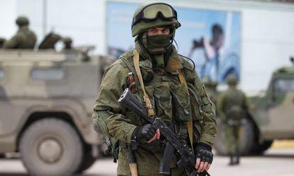 Un hombre armado cerca de los vehículos militares rusos situados en la frontera con Ucrania.