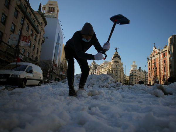 DVD 1036 (12-01-21) Nieve en el centro de Madrid por el temporal Filomena. Una persona, con su coche a la izquierda averiado, intenta romper hielo con una pala, en la calle Alcala. Foto Samuel Sanchez