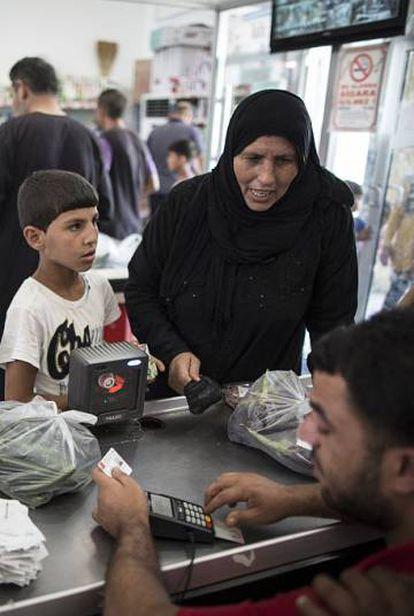 Refugiados compran con una tarjeta de la Media Luna Roja en Sanliurfa (Turquía) en 2015.