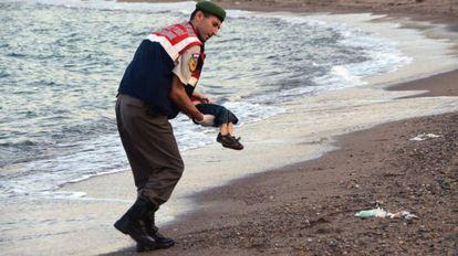 Un policía recoge el cadáver de un niño en una playa de Turquía.