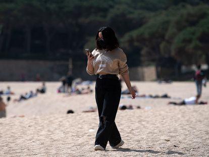 Una mujer pasea mientras consulta su teléfono móvil por la playa de Castell-Platja D'Aro, cerca de Girona, este miércoles.