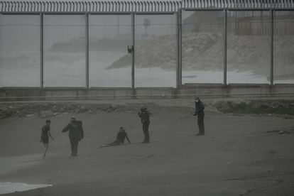 Dos jóvenes migrantes marroquíes en la playa del Tarajal (Ceuta), después de nadar desde la ciudad de Castillejos (Marruecos), el 24 de abril.