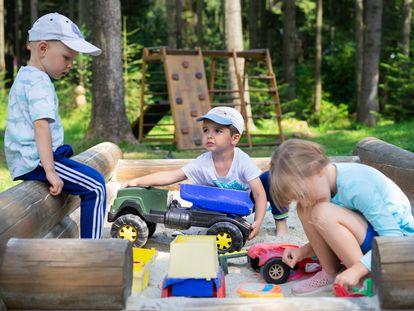 Tres niños se divierten en un parque de arena.