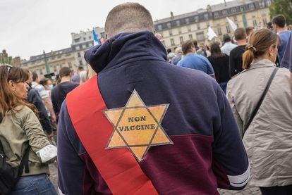 """Un manifestante en París el 17 de julio con una estrella de David en la espalda con la frase """"no vacunado""""."""
