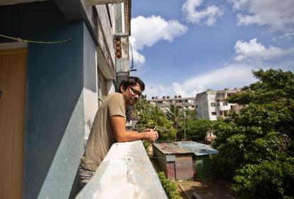 Yunior García, actor y dramaturgo cubano, se asoma a la calle desde el edificio donde vive en la Habana, Cuba, el día 15.