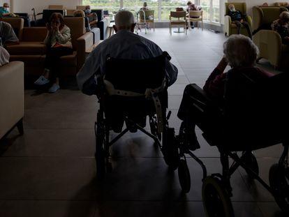 Residentes de un centro de mayores de la Comunidad de Madrid charlan y descansan en un salón del centro.