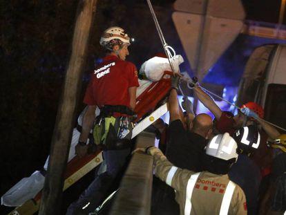 Los bomberos mueven el cuerpo de un hombre que fue arrastrado por la corriente.