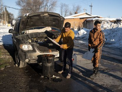 Isaac y su hijo avivan una estufa para calentar el motor del coche que se ha congelado, en el sector 6 de la Cañada Real. David Expósito