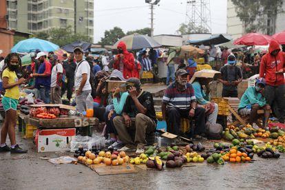 Vendedores trabajan bajo la lluvia en el mercado de Coche de Caracas.