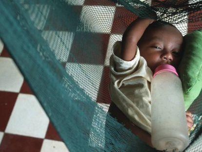 Un huérfano por culpa del sida, tumbado sobre una mosquitera.