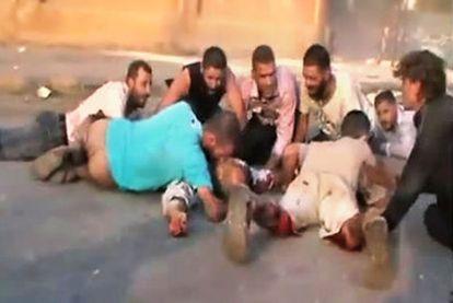 Varias personas se ponen a cubierto del tiroteo atribuido al Ejército en Hama, en una imagen captada de un vídeo   colgado en YouTube.