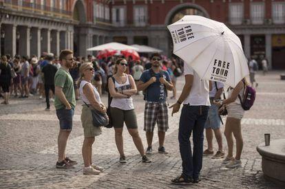 Un grupo de turistas escucha a un guía de un free tour en la plaza Mayor.