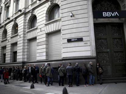 Fila frente a una sucursal del BBVA en Argentina, este lunes antes de la apertura. En vídeo, varias entrevistas con clientes de los bancos.