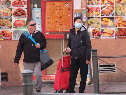 Dos vecinos del madrileño barrio de Usera, uno de ellos de origen chino que se protege con una mascarilla del brote de Covid-19.