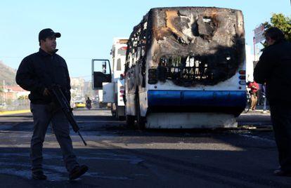 Autoridades junto a uno de los autobuses incendiados durante el operativo