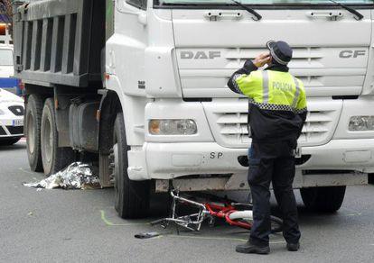 Un policía, en el lugar del accidente donde ha fallecido una ciclista, antes del levantamiento del cadáver