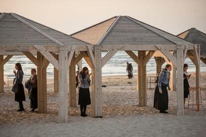 Jóvenes religiosas rezando bajo unas casetas en una playa de Tel Aviv.